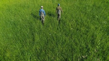 Fishermen walking on green high grass