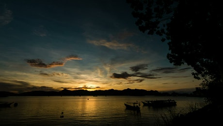 Fishing boats silhouetted during sunrise