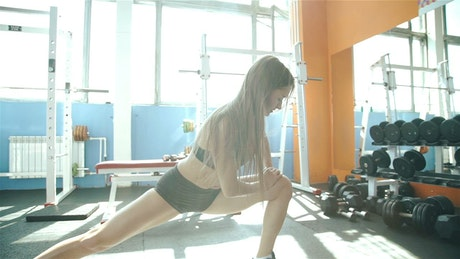 Fitness girl stretching her body before training in the gym