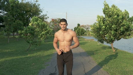 Fitness man running shirtless in the park