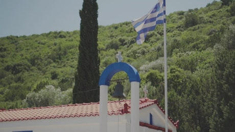 Flag of Greece waving on the dome of a church