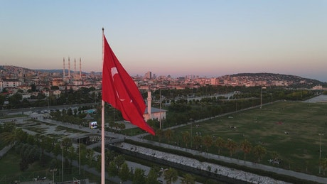Flag on a pole on top of a city in Turkey