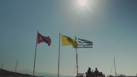 Flags flying in front of a stone wharf