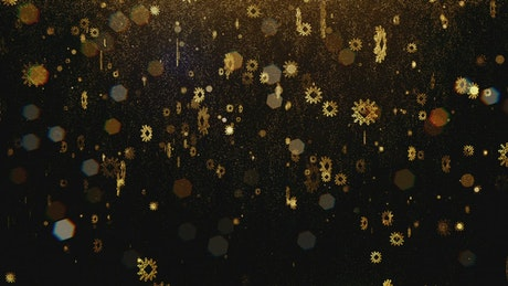 Flickering golden snowflakes on black background