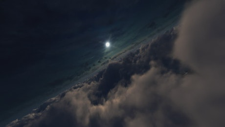 Flight through clouds towards the bright full moon