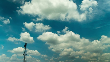 Fluffy clouds over a broadcast tower