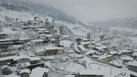 Flying above a town with old towers covered in snow