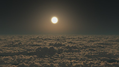 Flying above the clouds during a full moon