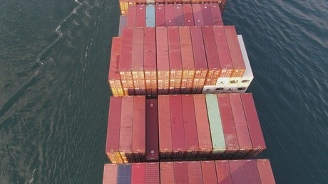 Flying over a cargo ship leaving a port