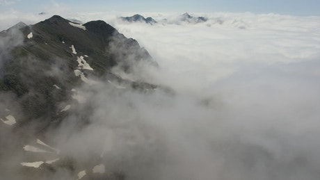 Flying over a cloudy mountain range