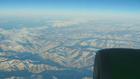 Flying over a range of mountains with snow