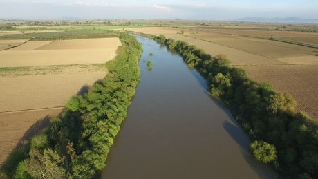 Flying over a river between agricultural fields
