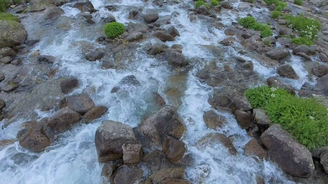 Flying over a stream with rocks