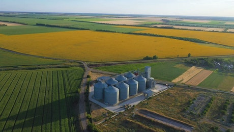 Flying over grain silos and sunflower fields
