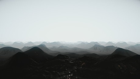 Flying over silhouettes of mountains on a planet