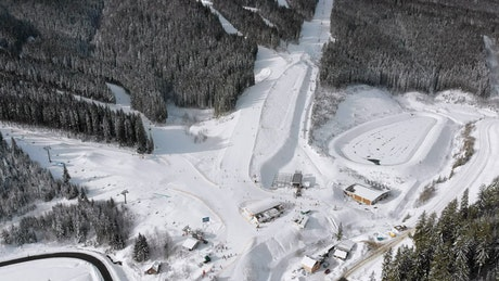 Flying over the mountain with ski tracks
