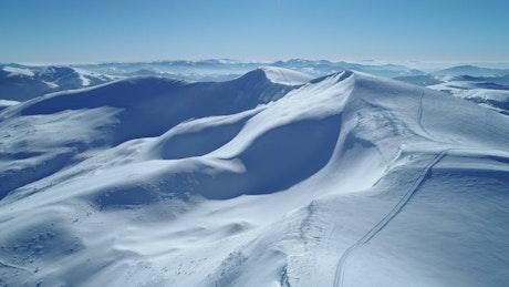 Flying over turquoise snowy mountain range