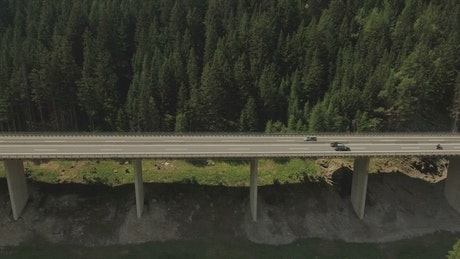 Flyover of tall mountain highway along river