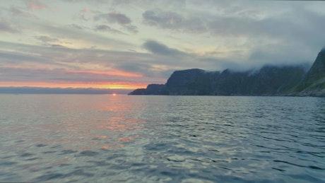 Flyover sea at sunset along mountain coast