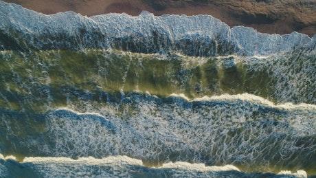 Foamy ocean waves colliding with a shoreline