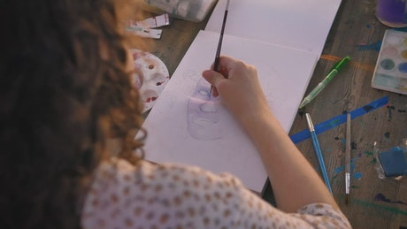 Focus on the hand of an artist girl painting with watercolor