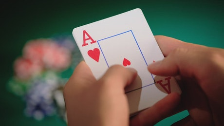 Focus on the hands with cards of a poker player