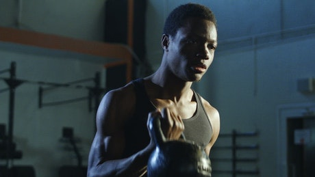 Focused athlete lifting a heavy kettlebell