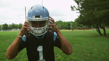Football player putting on a blue helmet