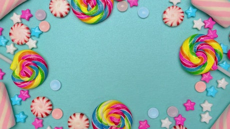 Frame of candies, lollipops and chocolates on a blue background