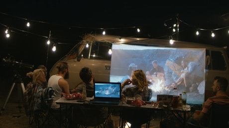 Friends camping watching a film on a projector