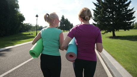 Friends carrying Yoga mats to the park
