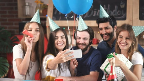 Friends celebrate birthday and take selfie at party