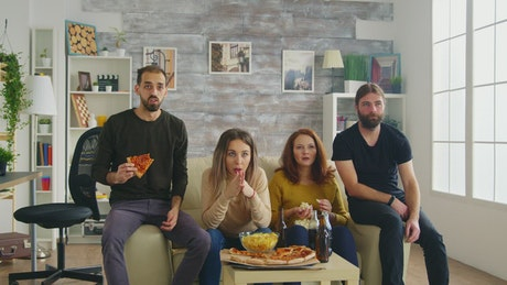 Friends celebrate sports victory on sofa with pizza