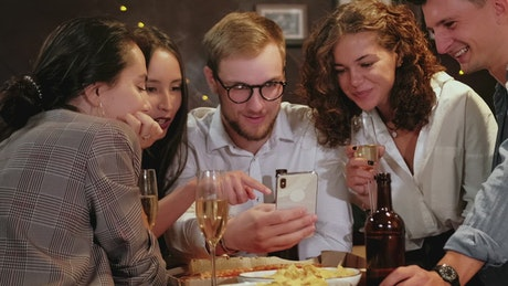 Friends celebrating a special date look at a cell phone