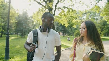 Friends chat while walking through sunlit park
