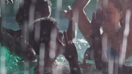 Friends dancing in a pool