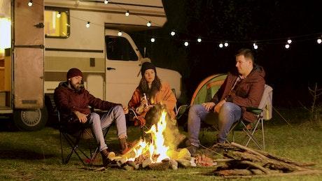 Friends enjoy a quiet night around a campfire