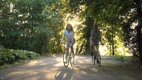 Friends enjoy sunny bike ride in park