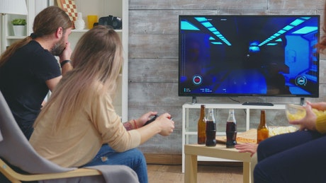 Friends enjoy video gaming on sofa at party