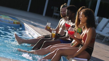 Friends enjoying a drink by the pool