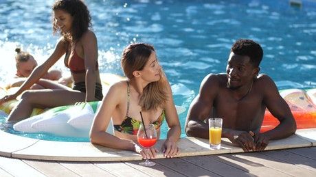 Friends enjoying cold drinks in the pool