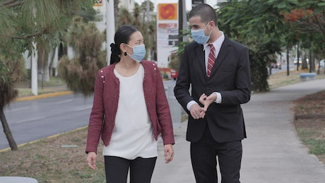 Friends in masks talking and walking on the street