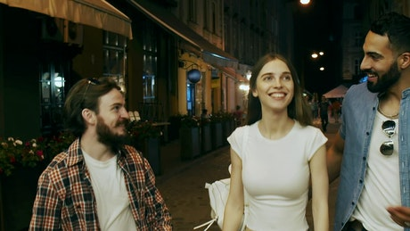 Friends laugh and walk down city street at night