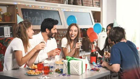 Friends laugh over champaign at birthday party