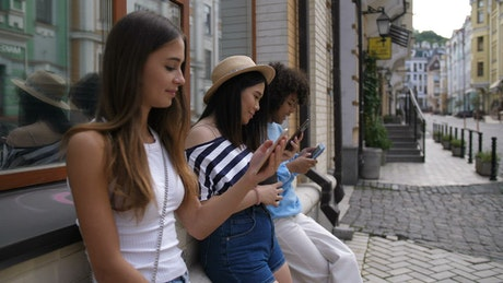 Friends on the street while using cell phones