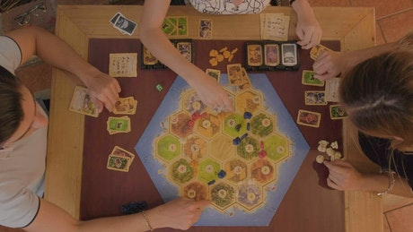Friends playing Catan sitting at a table