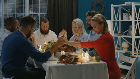 Friends praying before Thanksgiving dinner