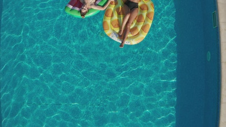 Friends relaxing on pool inflatables