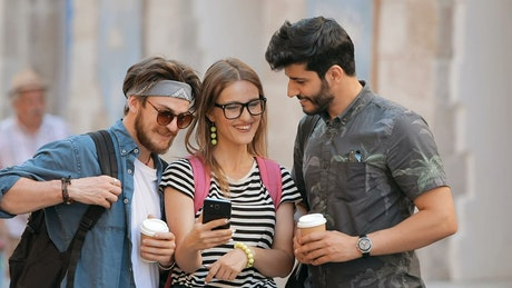 Friends smile at selfies on mobile phone