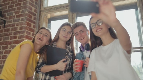 Friends smile for group selfie in front of sunlit window